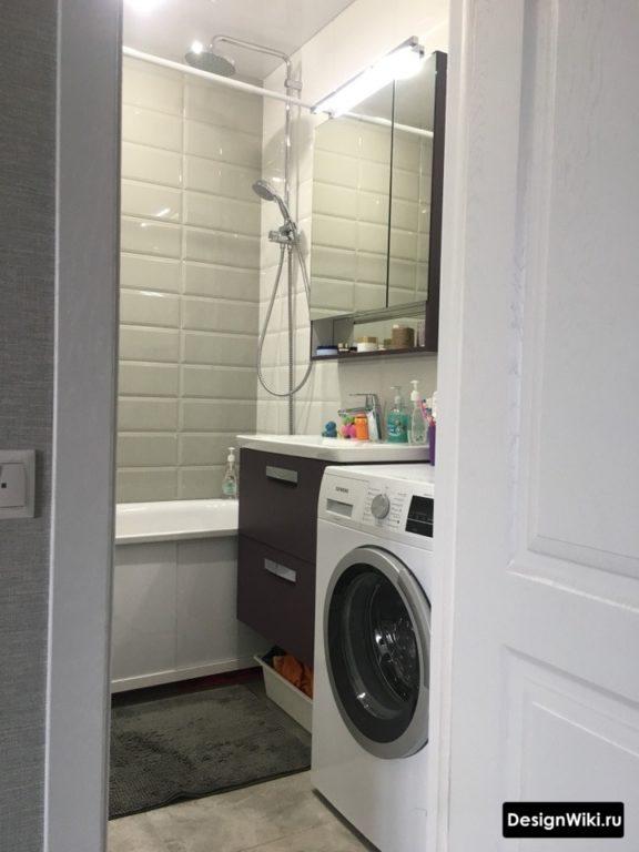 Carreaux de briques brillantes blanches dans la salle de bain à Khrouchtchev avec une machine à laver