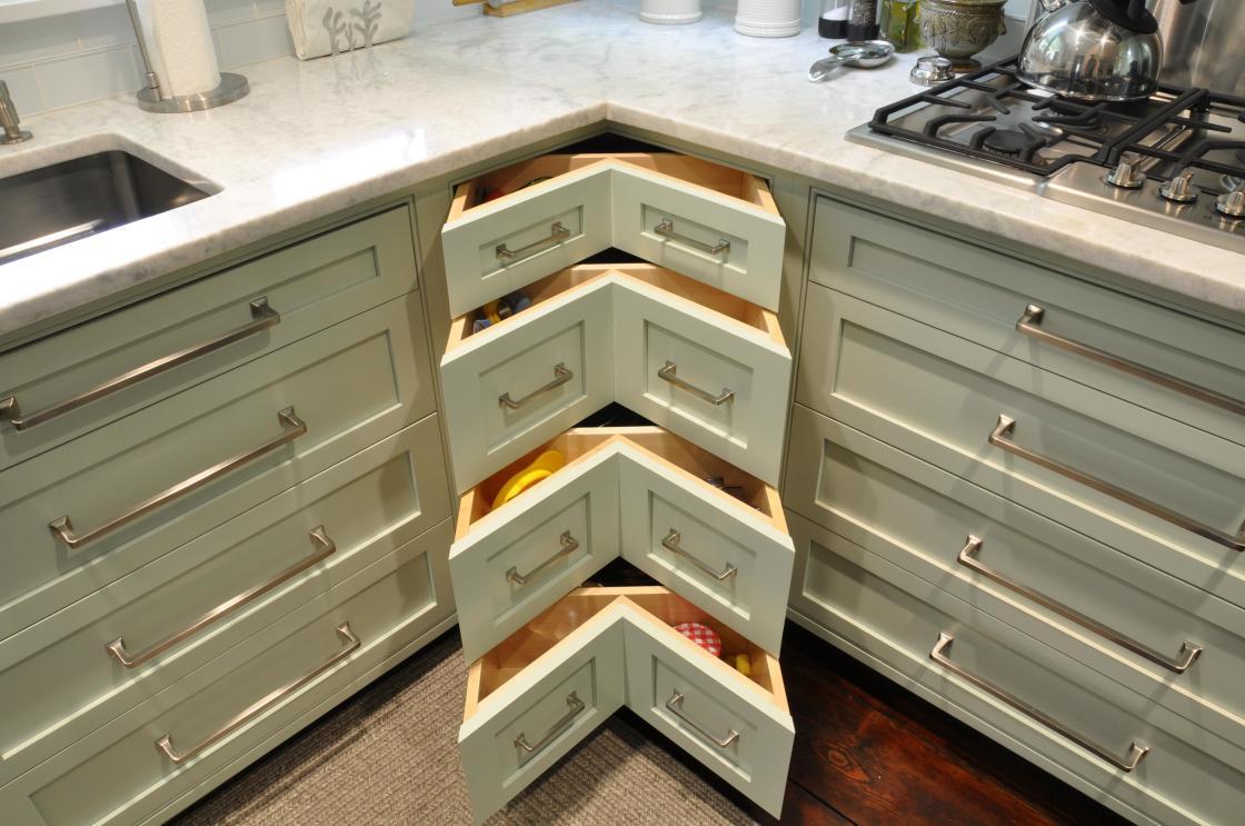 design-créatif-intérieur-de-la-base-armoire-de-cuisine-en-bois-poli-blanc-antique-avec-tiroirs-uniques-en-forme-de-coude-utilisant-de-longues-poignées-de-tirage-en-acier-inoxydable-1120x743