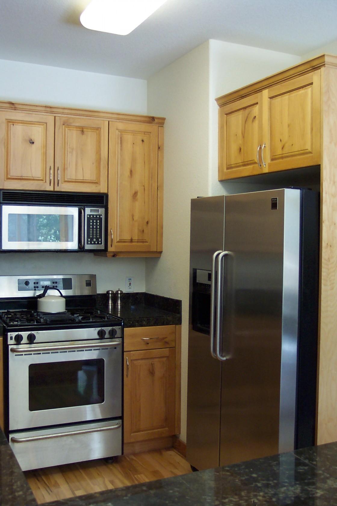 petites-idées-de-cuisine-avec-une-finition-marron-armoire-de-cuisine-en-pin noueux-utilisant-un-comptoir-en-granit-et-un-grand-frigo-en-acier-inoxydable-plus-micro-ondes-au-dessus-de-la-cuisinière-1120x1680