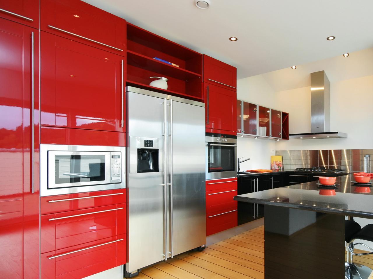 big-metal-refigerator-in-red-kitchen-armoires-face-black-countertop-on-wood-floor