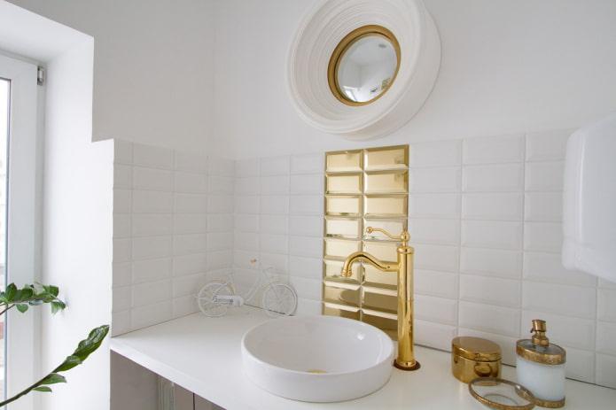 carreaux blancs et or à l'intérieur de la salle de bain